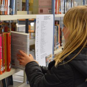 A child choosing a book off a library shelf