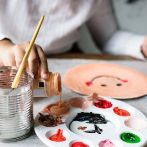 Creative Activities: A child pouring paint into a tray
