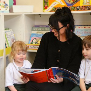 Teacher reading book to St Peter's Prep pupils