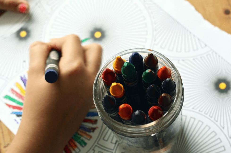 A pot of crayons with a child drawing