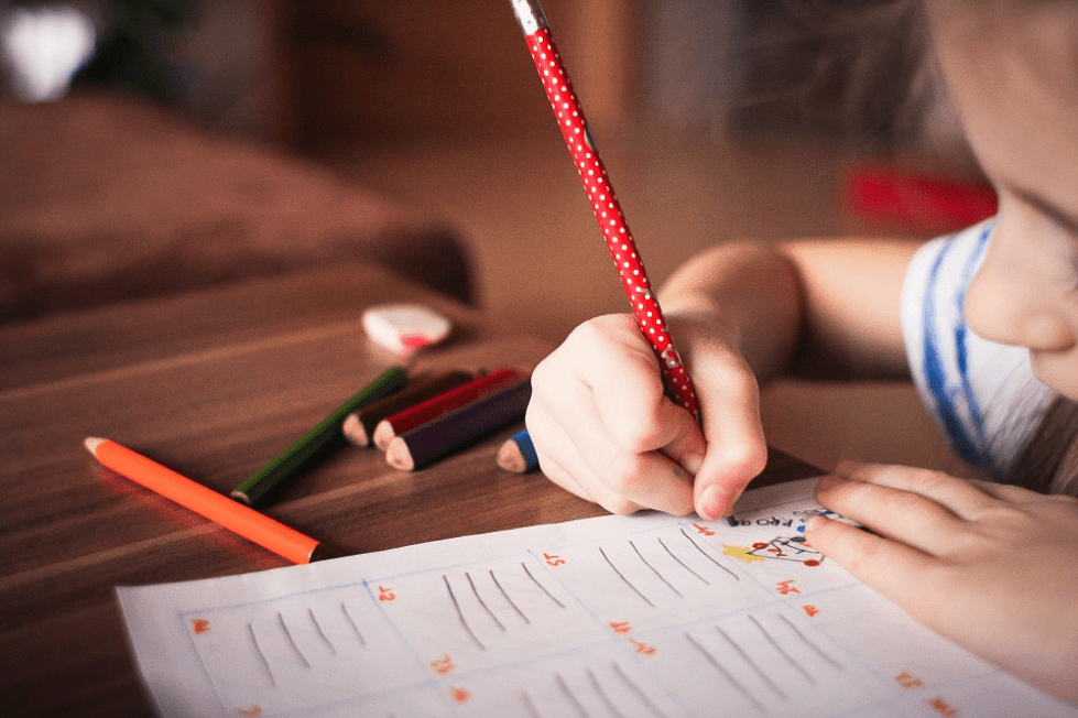 A child writing and colouring at a table