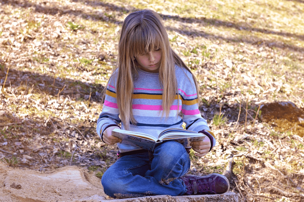 A girl sat outside with a book reading on the floor