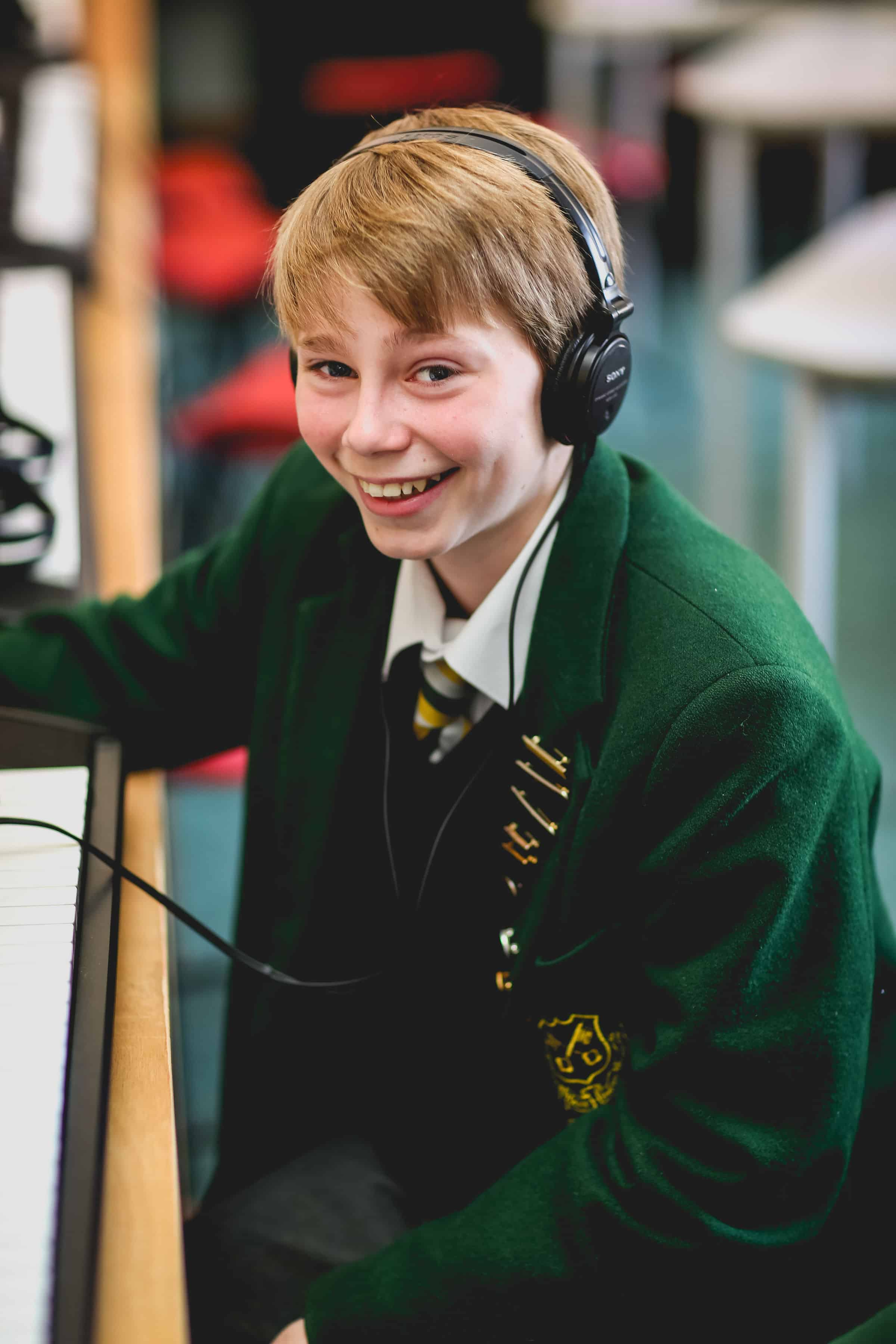 A boy smiling with headphones on