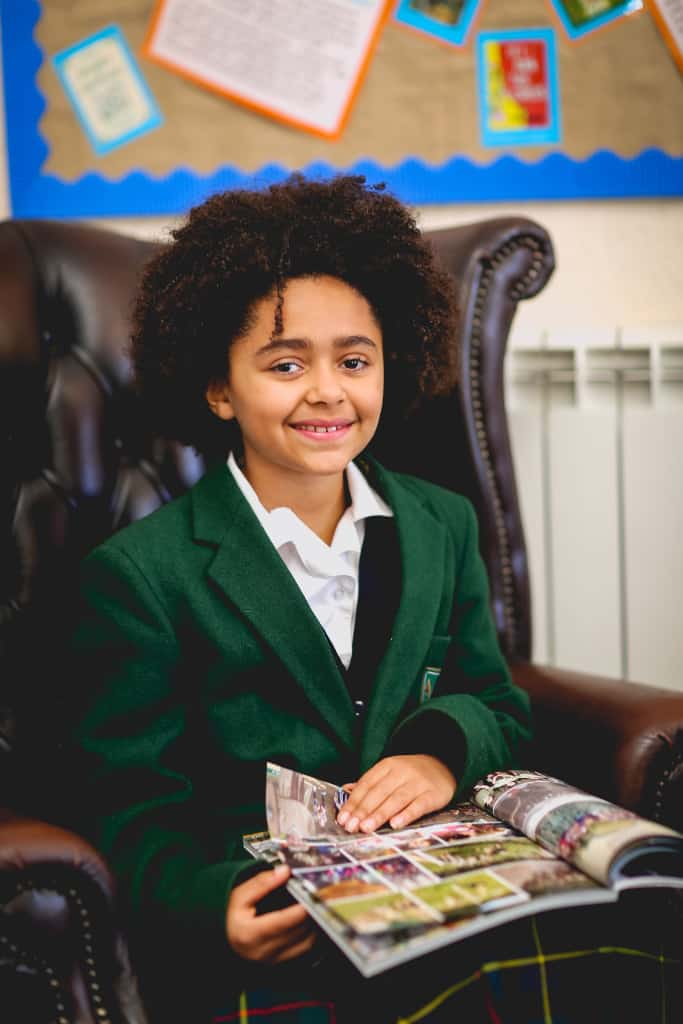 A girl sitting on a chair in school with a magazine on her lap, smiling