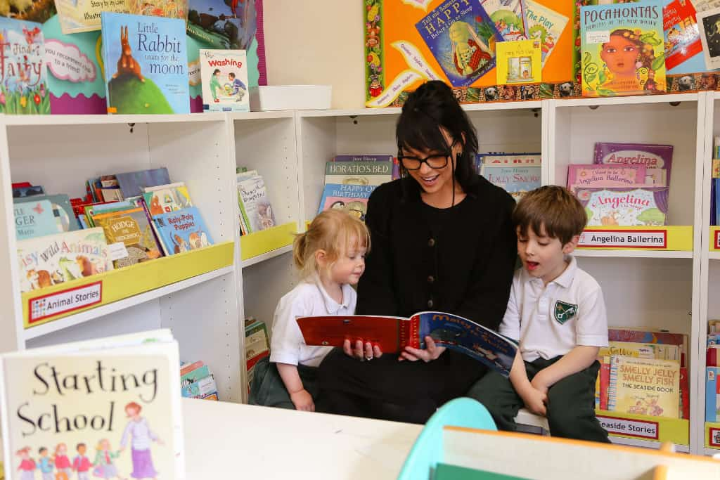 A teacher is reading a book to a girl and a boy in school