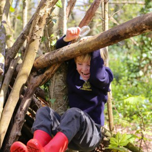 boy swinging in the tree at school with red wellies on