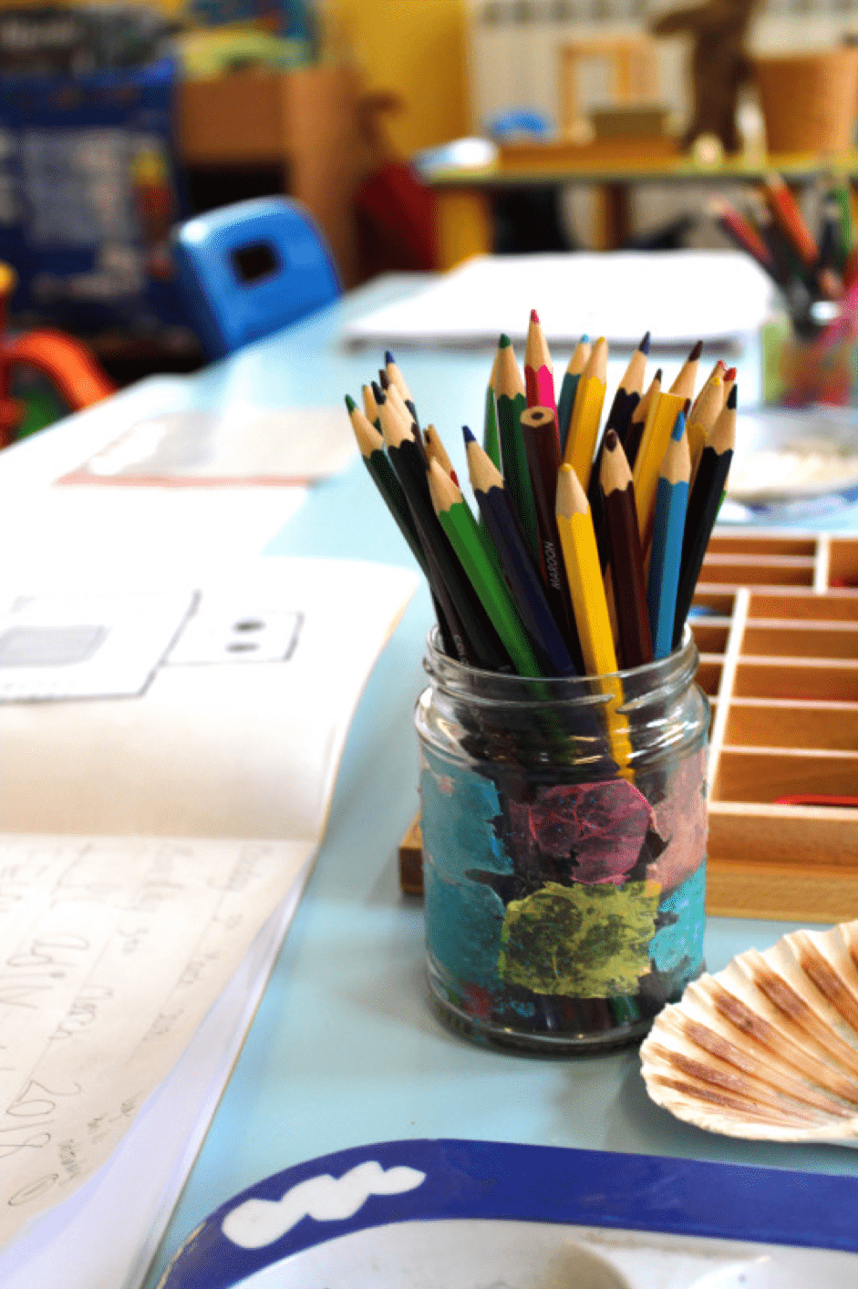 glass pot of colourful pencils on a desk