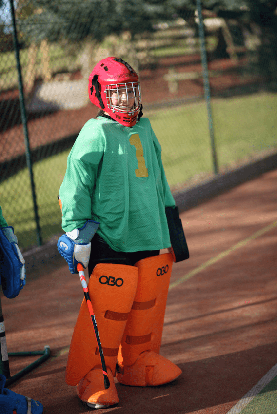 Girl standing in a hockey outfit on the pitch