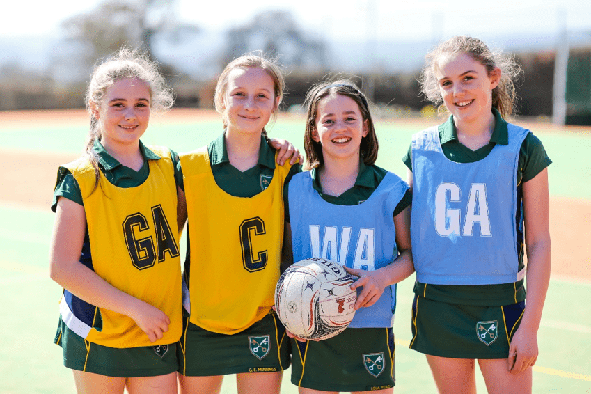4 girls stood on a school pitch with a football