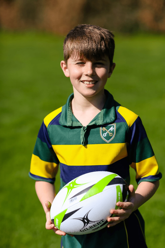 A boy stood on the pitch with a rugby ball