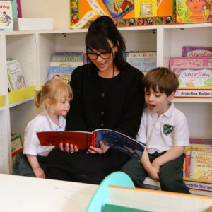 a teacher reading a book to two children