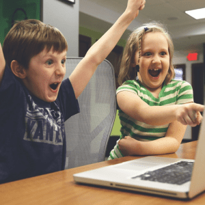 A picture of two children at a computer cheering