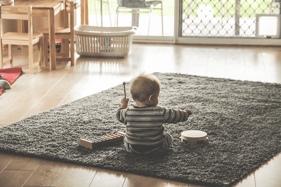 A picture of a baby on a rug with some musical instruments