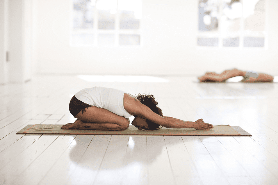 A picture of a lady on a yoga mat on the floor
