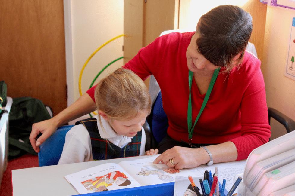 An HLTA helping a child read.