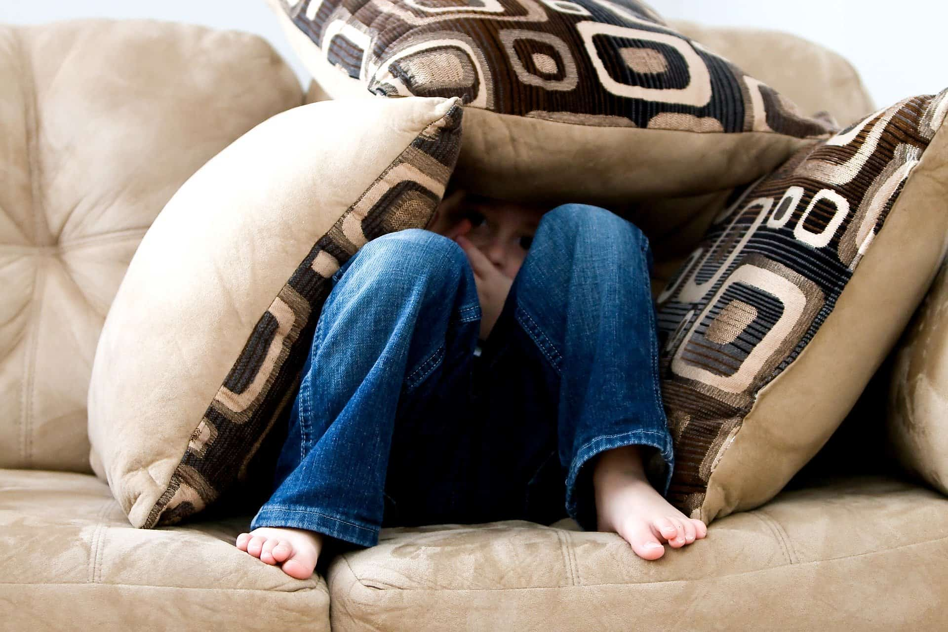 A little boy hiding underneath cushions