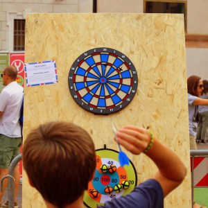A child throwing Velcro darts at a board at a school fair