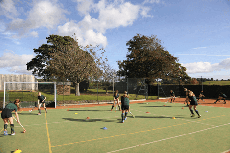 Young children playing field hockey at St Peter's Prep School