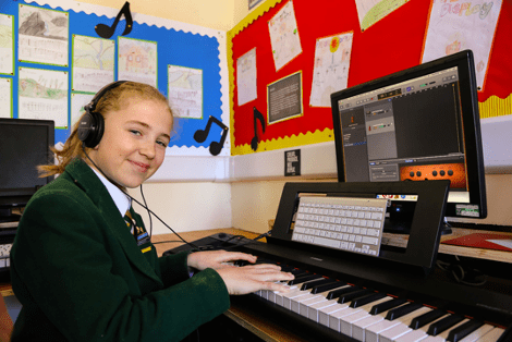 A young girl learning the piano at St Peter's Prep School