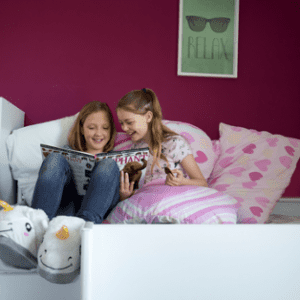 Two young girls in slippers on a sofa reading a magazine