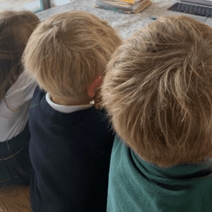 Three young siblings looking at something sat next to each other