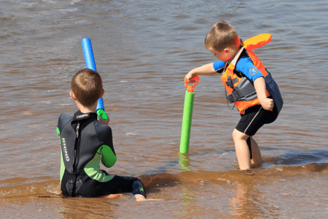 Two young siblings playing at the beach together