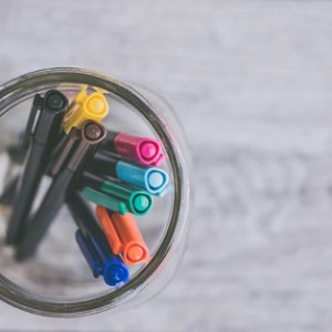 A glass pot with colouring pens in