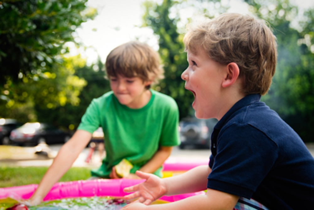 Two young children playing at a family picnic