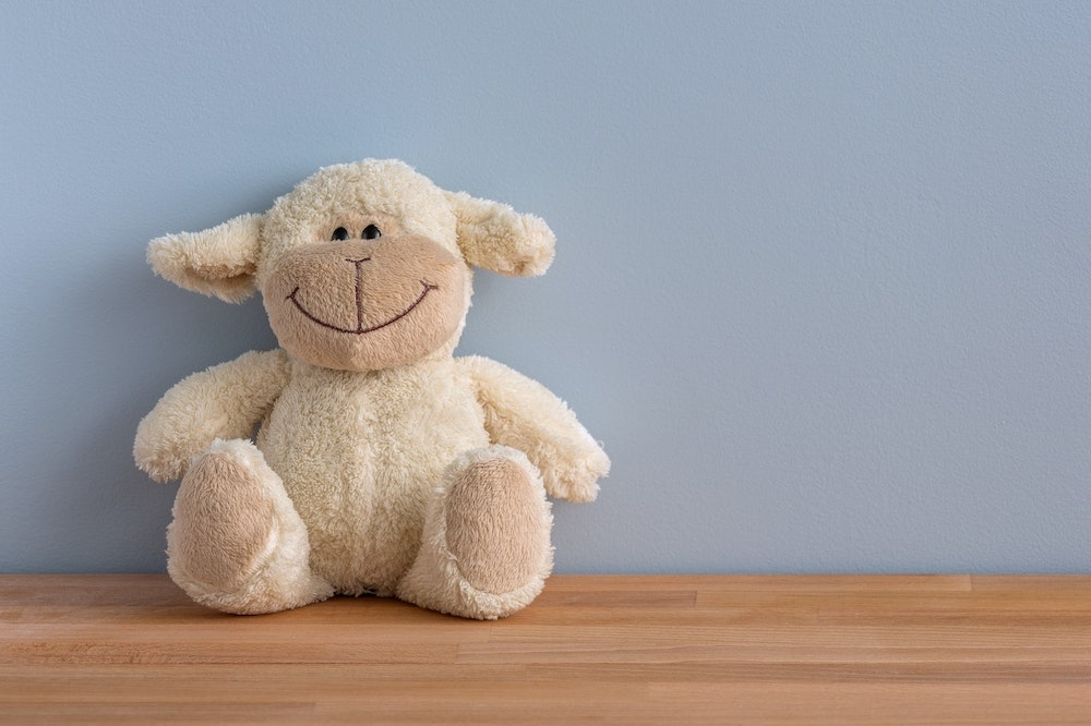 A cuddly toy leaning on a blue wall
