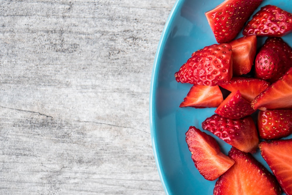 Strawberries sliced in a blue bowl