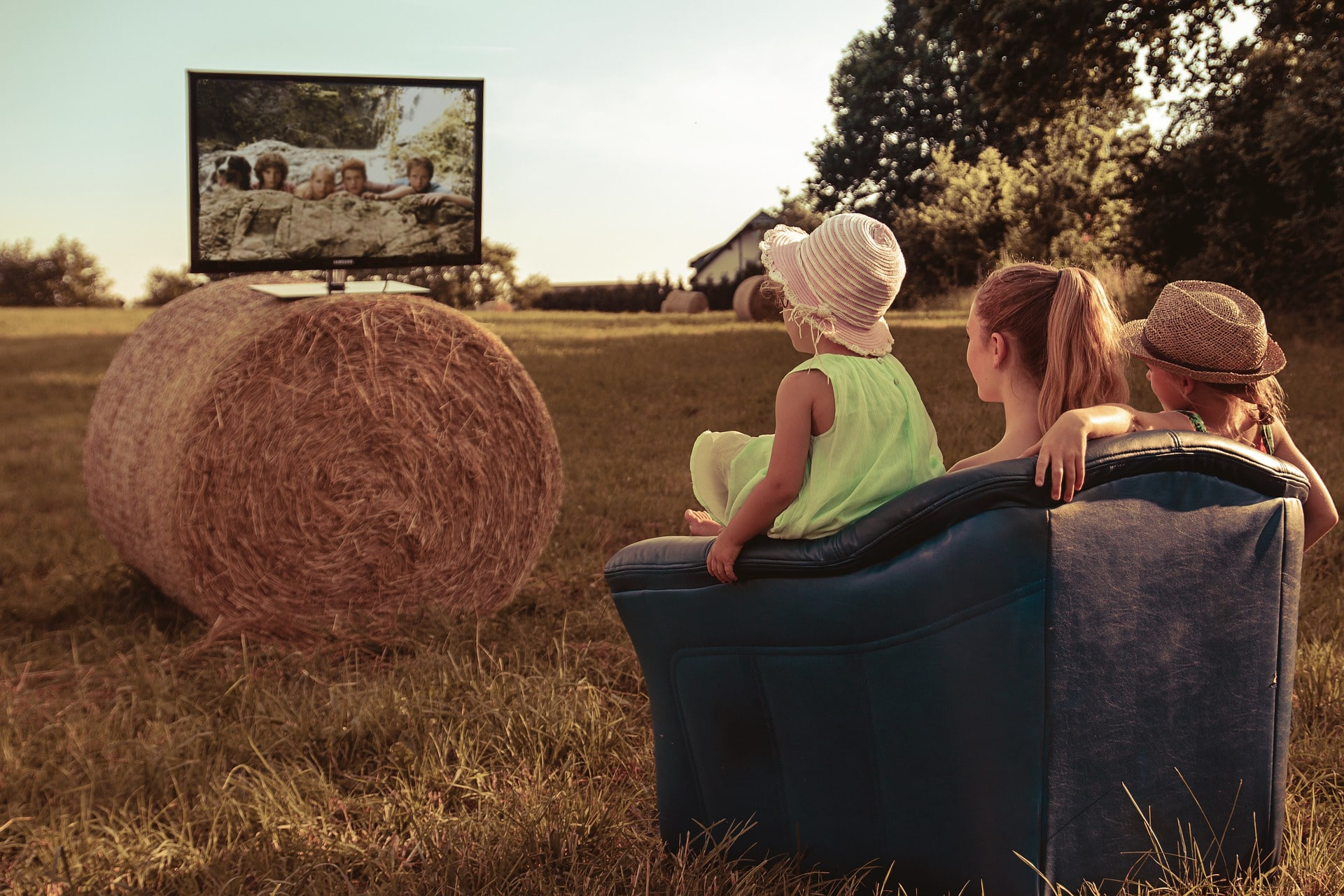 a family watching tv outside